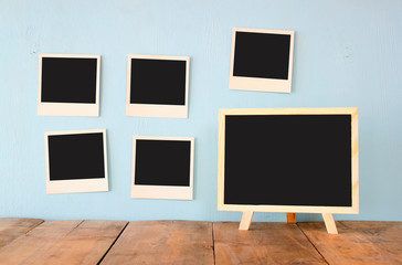 blank instant photos hang over wooden textured background next to blank blackboard