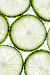 green lime slices and ice cubes, top view