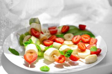 Fresh fruits on skewers in plate on table, closeup