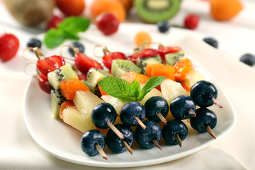 Fresh fruits on skewers in plate on napkin, closeup