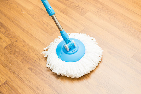 Cleaning wood floor by modern mop.