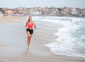 young sporty woman runs along the coastline at the morning