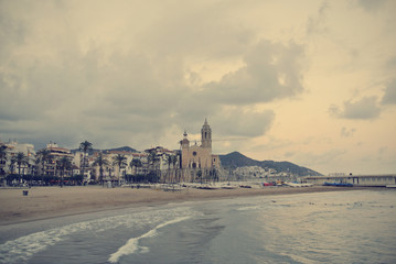 Picturesque little Spanish seaside resort Sitges, on Costa Dorada, on a cloudy afternoon in early fall. Image filtered in faded, retro, Instagram style; nostalgic, vintage travel concept.
