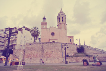 Architecture of the small Spanish seaside town Sitges, on Costa Dorada, on a cloudy afternoon in early fall. Image filtered in faded, retro, Instagram style; nostalgic, vintage travel concept.