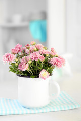 Beautiful flowers in vase on table, on light background