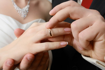 hand of groom putting a ring on finger of his bride