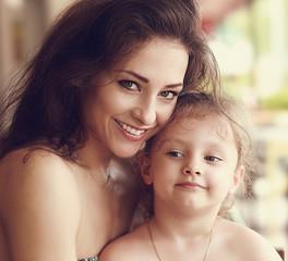 Fototapeta Happy smiling mother cuddling her cute daughter. Closeup toned p obraz