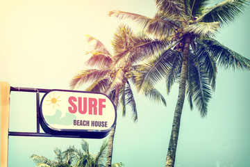 Fototapete - Vintage surf beach house signage and coconut palm tree on tropical beach blue sky with sunlight of morning in summer,  instagram retro filter