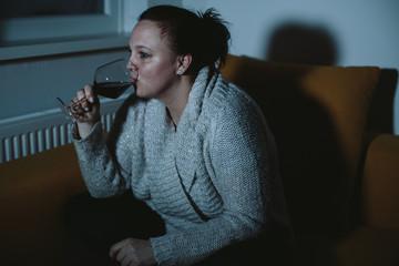 Overweight woman watching TV drinking wine