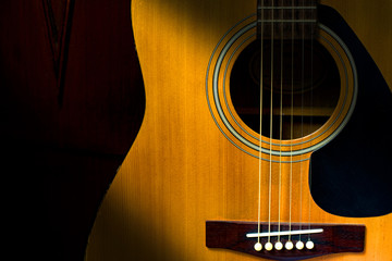 Detail of acoustic guitar in dark room with retro filter effect
