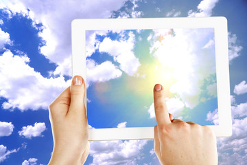 Hands holding tablet PC and pointing on screen on sky background