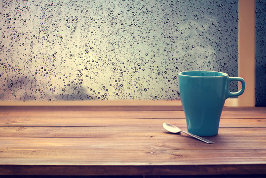Hot coffee cup on wood table with raindrop window, relax time (vintage color tone)
