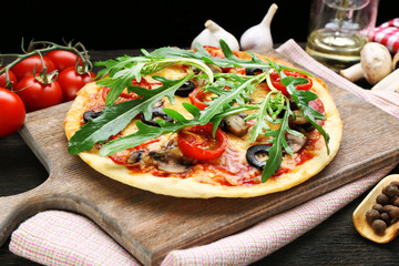 Tasty pizza with vegetables and arugula on cutting board on table close up