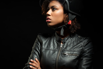 Woman in a motorcycle helmet and leather jacket on a black background