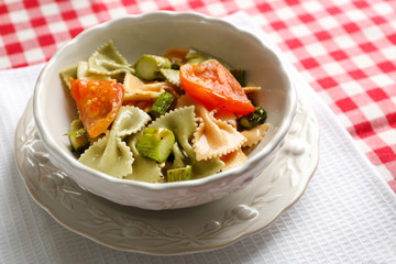 Roasted asparagus and tasty pasta with vegetables in bowl on wooden table background