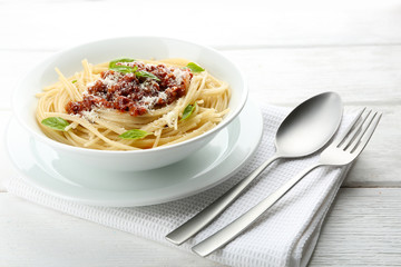 Spaghetti Bolognese with parmesan cheese in white bowl, on color wooden background