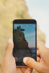 Close up on male hands taking photo of sea coast with mobile cell phone. Summer beach holiday vacation concept