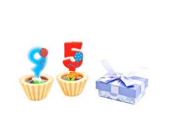 cakes with ninety five years birthday candles and gift on white