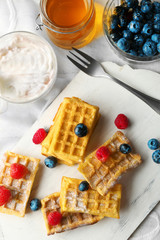 Sweet homemade waffles on tray, on light background