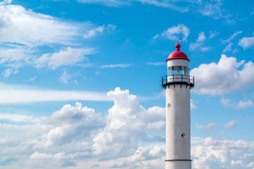 Brick white lighthouse with red top against blue sky with clouds in Hellevoetsluis, the Netherlands