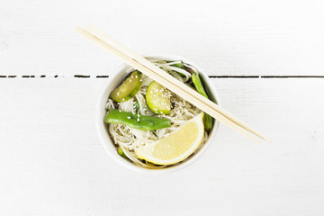 Asian noodles with siliculose haricot, zucchini and lemon on whi