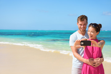 Couple Taking Selfie On Mobile Phone At Beach