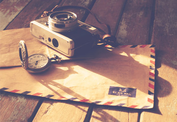Vintage travel background, old film camera ,antique watches and airmail letter on wood table, instagram effect filter