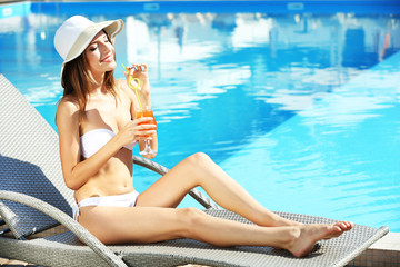 Young woman resting on sunbed with cocktail at swimming pool