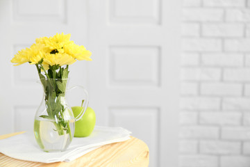 Beautiful flowers in decorative vase on light background