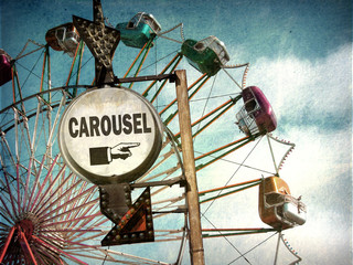aged and worn vintage photo of carousel sign with ferris wheel