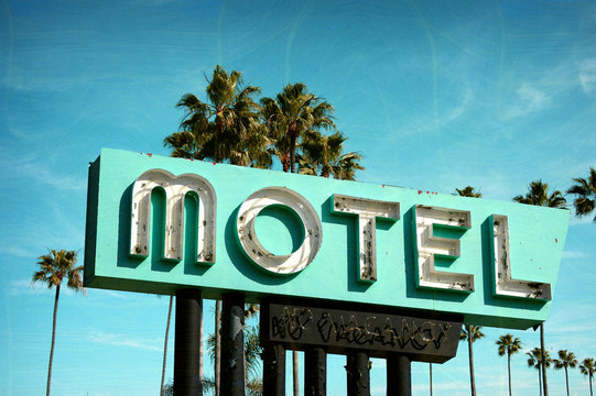 aged and worn vintage photo of old neon motel sign with palm trees