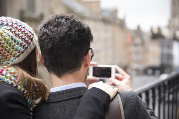 Rear view of a couple using a Smart Phone to take a photograph.