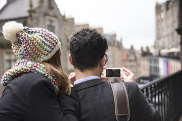 Rear view of couple using a Smart Phone to take photograph.