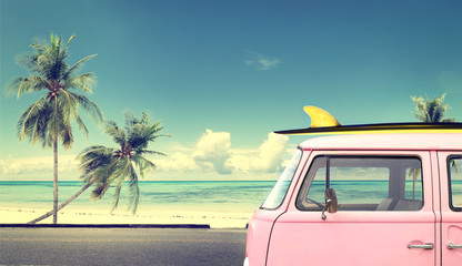 Wall Mural - Vintage car in the beach with a surfboard on the roof