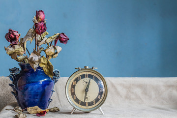 Clock and a vase on a white background.
