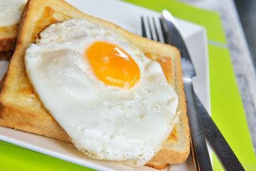 Dish croque-madame with beautiful fried eggs, bread and ham, shallow DOF in natural light closeup image