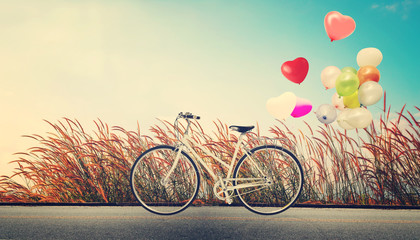 Wall Mural - bicycle vintage with heart balloon on wild flower field and blue sky concept of love in summer and wedding honeymoon