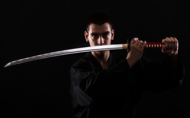 Young martial arts fighter with katana on black background Wall mural