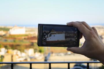 Hombre haciendo fotografía a monumento con teléfono movil