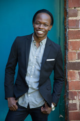 Happy Black man outdoors smiling in a suit coat