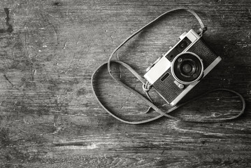 Retro camera on wood table background, black and white color tone