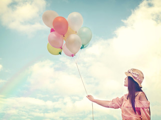 Wall Mural - Vintage photo of  Happy young red hair woman  holding colorful balloons and flying on clouds sky background.