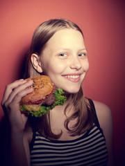 Teen girl eating a burger