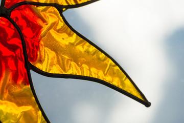 Closeup of a yellow glass sun ornament against a blue sky