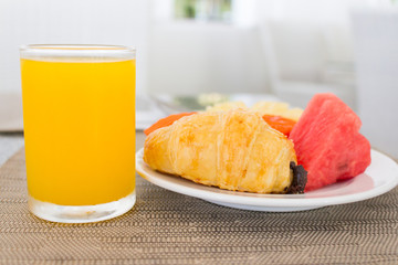 Breakfast with orange juice, croissant and fruits