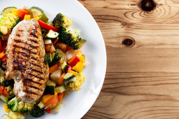 Grilled chicken fillet, breast with cooked vegetable Tomatoes, Carrots, Peppers, Courgettes, brocoli on plates.
