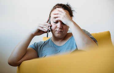 Pensive overweight woman talking on phone