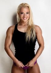 Smiling blond woman in black sportswear.