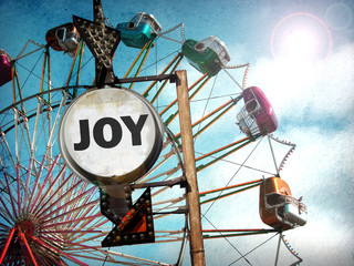 aged and worn vintage photo of ferris wheel and joy sign with bright sun flare