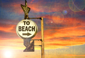 aged and worn vintage photo of to beach sign with sunset and bright sun flare